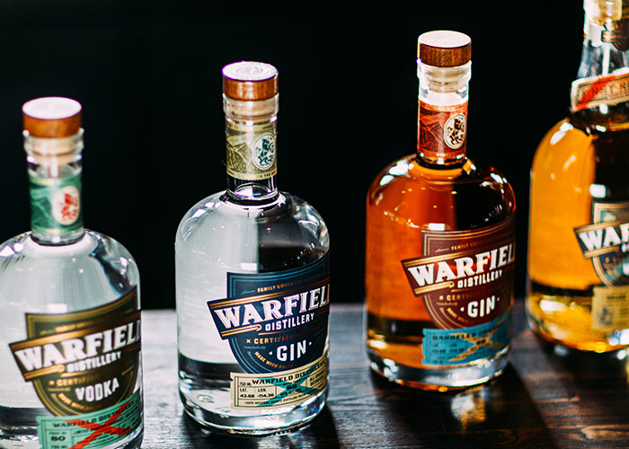 lineup of Warfield vodka, gin, barrel aged gin, and whiskey bottles