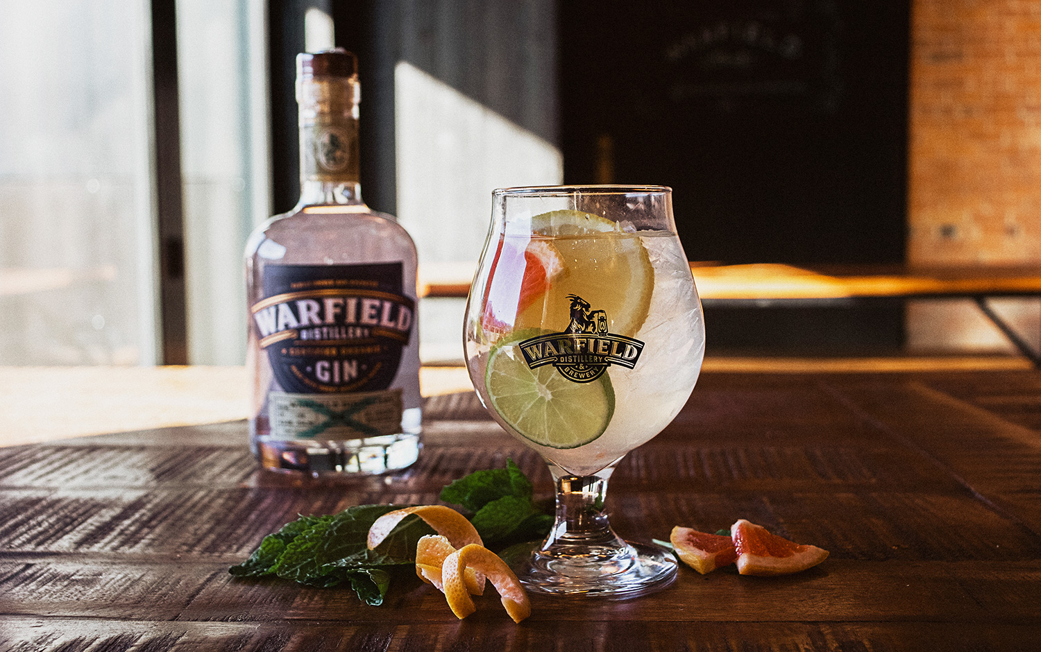 Warfield cocktail garnished with fruit made with Warfield gin in the background